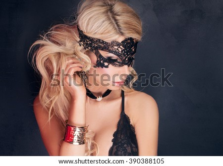 Sexy beautiful blonde woman posing in elegant black lingerie and mask. Perfect body.