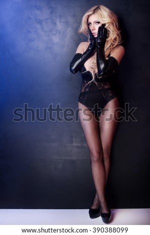 Sexy beautiful blonde woman posing in elegant black lingerie, looking at camera. Perfect body. Full photo. - stock photo