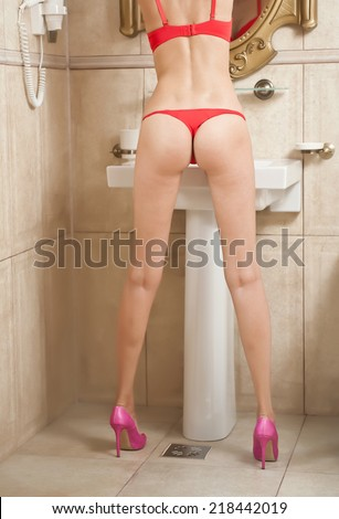 Sexy beautiful body shoot of young woman wearing red lingerie and high heels in bathroom. Woman body with long legs in front of the mirror in elegant bath room. Rear view of woman perfect body. - stock photo