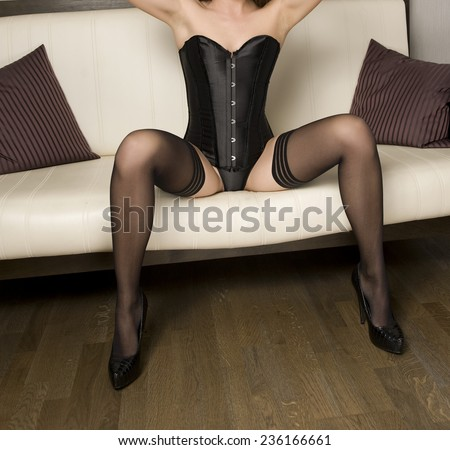Sexy beautiful body shot of young woman wearing black lingerie and stockings. Long legs in black stockings. Perfect body woman in black corset posing provocatively sitting on sofa, boudoir shot. - stock photo