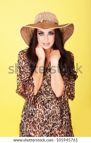 Sexy beautiful brunette in stylish straw hat and animal print dress posing against a yellow studio background - stock photo