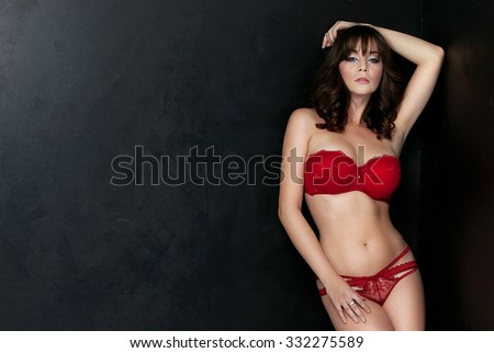 Sexy beautiful brunette lady posing in fashionable red lingerie. Sensual woman with glamour makeup. Studio shot. - stock photo