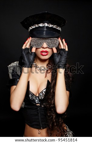 sexy beautiful  brunette semi nude police woman with long curly hair with handcuffs  with bright makeup and red lips isolated on black in fashion glasses