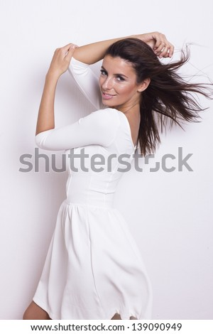 Sexy beautiful brunette woman in white dress on white background - stock photo