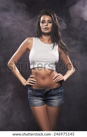 Sexy beautiful brunette woman posing in jeans shorts. Girl with perfect slim body.  - stock photo