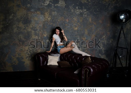 Sexy beautiful girl in jeans shorts, golf and white shirt on couch in interior studio. Fashion shooting