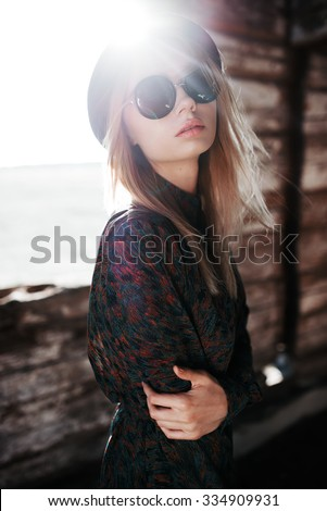 Sexy beautiful girl in round glasses and a hat against the sun