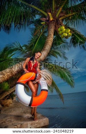Sexy beautiful girl posing with float tube on the beach - stock photo