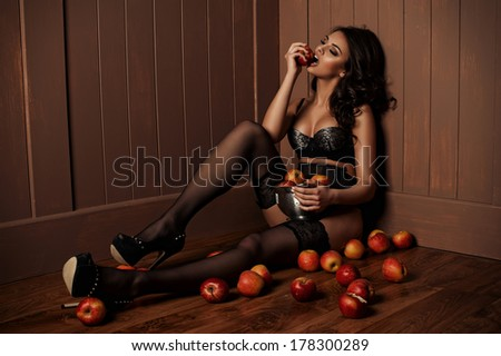 Sexy beautiful girl sitting on a floor with apple in the hand.  - stock photo