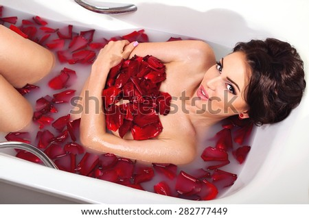 Sexy beautiful naked brunette woman laying in a bath with milk and red romantic rose petals looking at camera. Luxury spa and skin care - stock photo