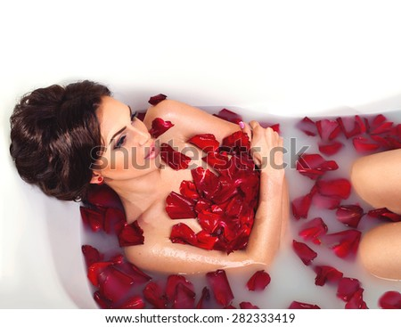 Sexy beautiful naked brunette woman laying in a bath with milk and red romantic rose petals. Luxury spa and body care - stock photo