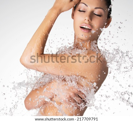 Sexy beautiful naked woman with wet body and splashes of water - stock photo