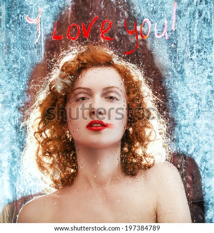 Sexy Beautiful Red haired Woman Behind Glass with Water Drops. Wet Glass in Drops with an Inscription I Love You - stock photo