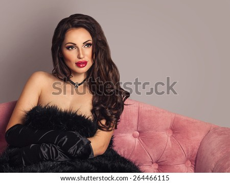 Sexy beautiful thoughtful brunette woman in black vintage gloves and fur on a luxury pink velvet sofa, dreaming. Bright grey background with copy space - stock photo