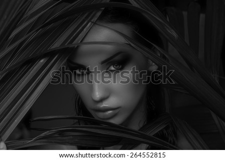Sexy beautiful woman hiding behind the palm leaves like a panther in the in the tropical forest in India. Portrait of beautiful caucasian stylish young woman with smokey eyes, wildness - stock photo