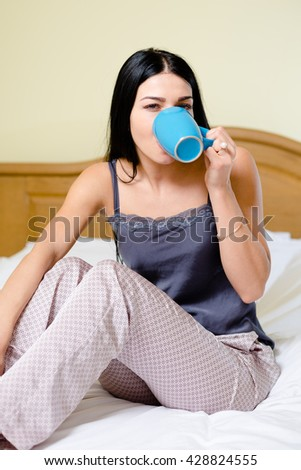 Sexy beautiful woman in bed drinking coffee tea, portrait close up