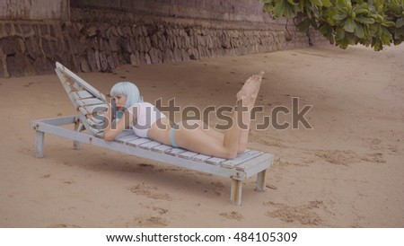 Sexy beautiful woman in modern futuristic style posing on the damaged wooden blue sunbed. Creative look of woman on the beach wearing bikini and blue wig