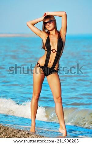 Sexy beautiful woman is sunglasses and black swimwear on sea coast - stock photo