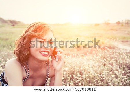 sexy beautiful woman using a smartphone in flower field in summer laugh so happy