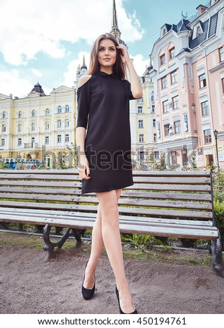 Sexy beautiful woman walk on the city street building bench park fashion luxury style for party date glamour pose summer clothes collection brunette hair accessory model wear black cotton dress hairdo
