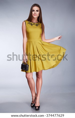Sexy beautiful woman wearing a dress, accessories shoes with high heels, fashion style design, makeup cosmetics hairstyle, slim body shape, clothing collection catalog bag yellow dress - stock photo