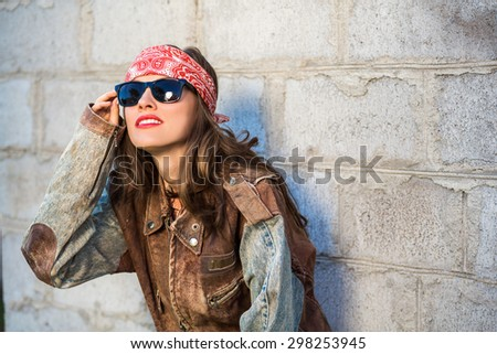 Sexy beautiful woman wearing leather coat, sunglasses and hairband over grey grunge vintage wall,  soft, focus on sunglasses and coat