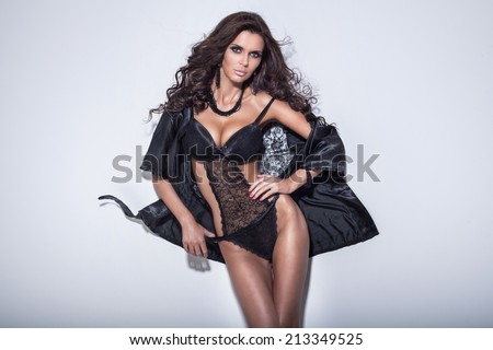 Sexy beautiful woman with long curly hair and slim body posing in sensual lingerie, looking at camera - stock photo