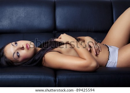 sexy beautiful young girl relax on black sofa - stock photo