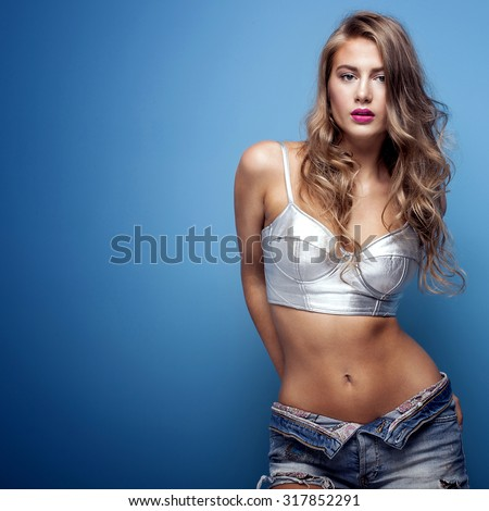 Sexy beautiful young woman posing on blue background, looking at camera. Girl in short jeans and silver fashionable top. Studio shot. - stock photo