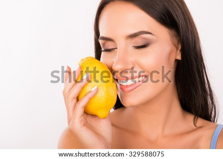 sexy beautiful young woman sniffing the scent of lemon - stock photo
