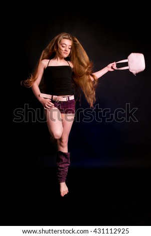 Sexy Beauty Girl. Fashion Blonde. Portrait of a girl a pink bag jump on a   black studio background - stock photo