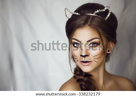 Sexy Beauty Girl with cat make up on her face and ears on her head. Provocative Make up. Luxury Woman with Green Eyes. Fashion Brunette Portrait  on a silver background. Gorgeous Woman Face. Long Hair - stock photo