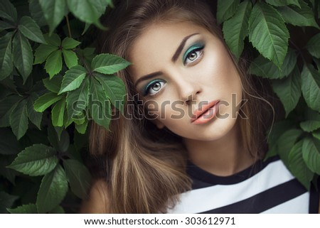 Sexy Beauty Girl with coral Lips. Provocative green Make up. Luxury Woman with Green Eyes. Fashion Brunette Portrait in wild leaves (grapes),  natural background. Gorgeous Woman Face. Long Hair - stock photo