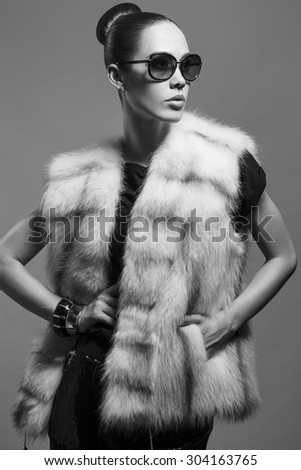 Sexy Beauty Girl with natural  Make up.  Fashion Brunette Portrait of a girl dressed in fur coat and black sunglasses posing on a grey background. Retro style. Monochrome (black and white)  photo - stock photo