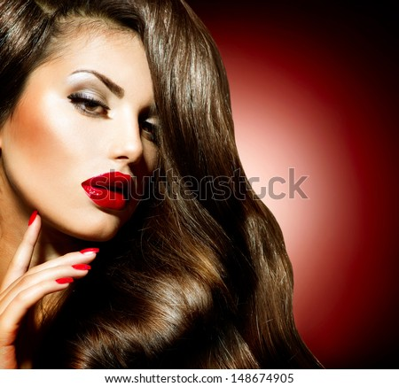 Sexy Beauty Girl with Red Lips and Nails. Make up. Luxury Woman with Long Curly Hair. Fashion Brunette Portrait on a red background. Gorgeous Woman Face.
