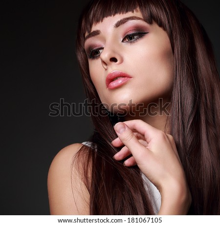 Sexy beauty woman face with long gloss hair on dark background. Closeup