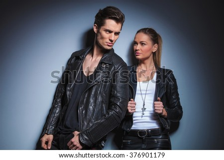 sexy biker pose looking away while his woman is starring at him arranging her leather jacket in studio background - stock photo