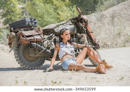 Sexy biker woman on the desert background