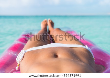 Sexy bikini body abs stomach closeup and tanned legs of beach woman relaxing tanning on air mattress bed on turquoise ocean or swimming pool at a tropical caribbean destination. - stock photo