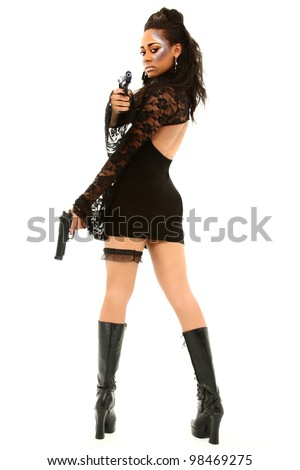 Sexy Black Female In Black Dress And Boots Aiming A Handgun At The Camera - stock photo