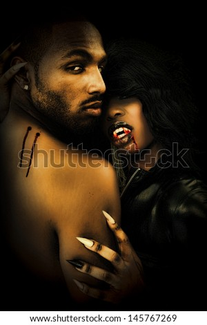 Sexy Black Vampire Couple in the Dark - stock photo
