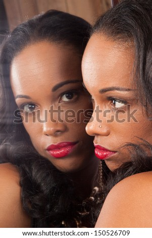 Sexy black woman in black shirt, looking into a mirror showing her own reflection - stock photo