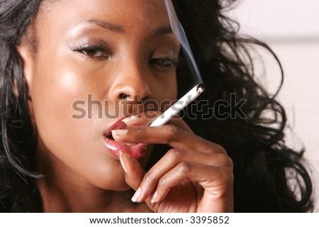 Sexy black woman smoking a cigarette - stock photo