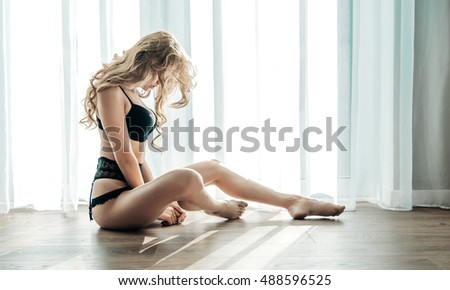 Sexy blond beauty posing at the window