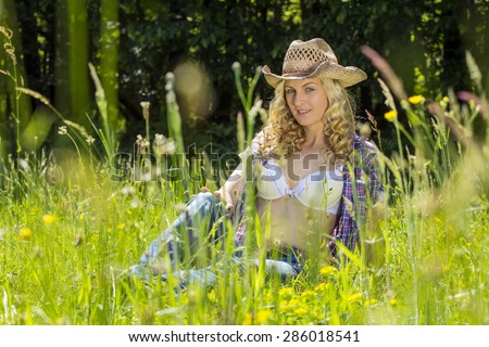 Sexy, blond farm girl sitting in a tall spring grass. - stock photo