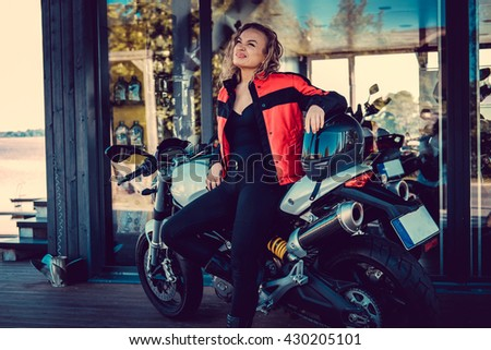 Sexy blond female in red leather jacket posing near motorcycle. - stock photo