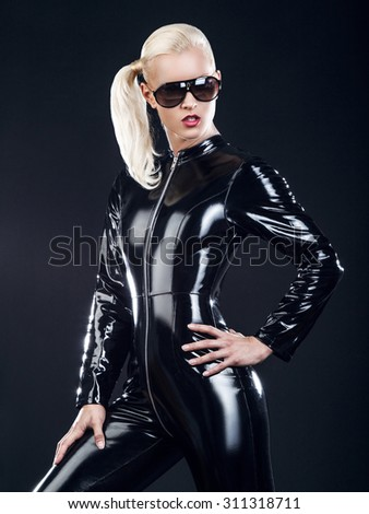 Sexy blond female in sunglasses and in latex black costume isolated on dark background. - stock photo