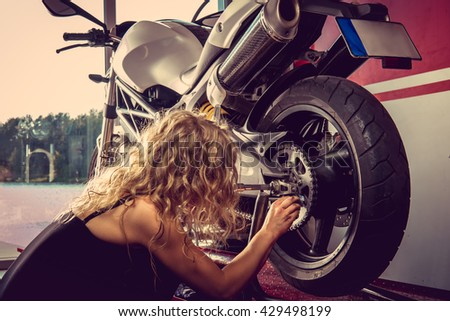 Sexy blond female repairing motorbcycle in a garage.