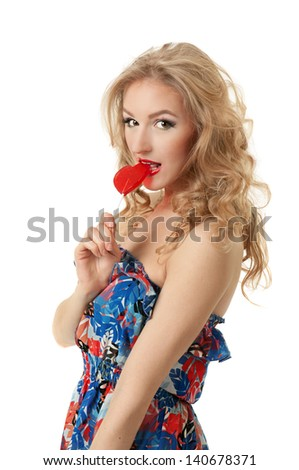 Sexy blond girl eating heart candy - stock photo