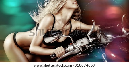 Sexy blond girl riding a motorcycle with speed - stock photo